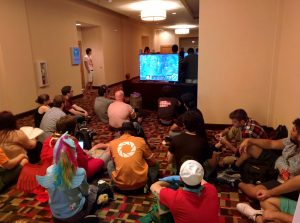 Group taking a break and watching a game of LoL